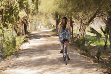 Young woman riding her bicycle away and surrounded by trees