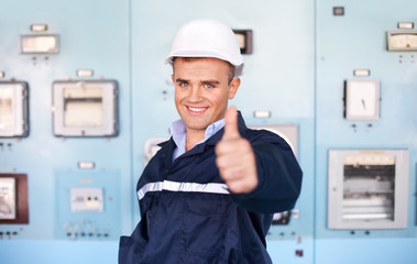 young engineer with thumbs up at control room