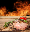 Grilled beef steak with flames on background