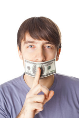 Young man with his mouth sealed by a hundred dollar bills isolat