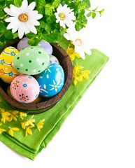 Easter eggs in the pot with flowers isolated on white background