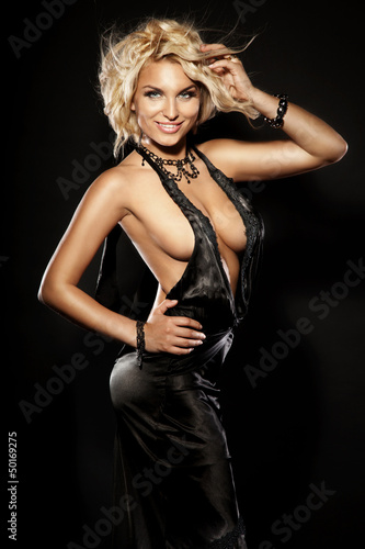 Smiling blonde sexy girl posing wearing black dress