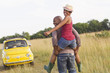 Man piggybacking wife in field near car