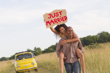 Man piggybacking wife who is holding just married sign