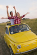Caucasian couple standing in car sun roof in field
