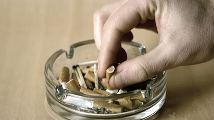 Man putting out cigarette in ashtray
