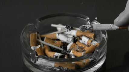 Hand tipping ash from cigarette into ashtray
