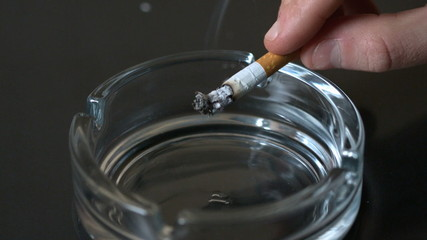 Hand tipping ash into empty ashtray