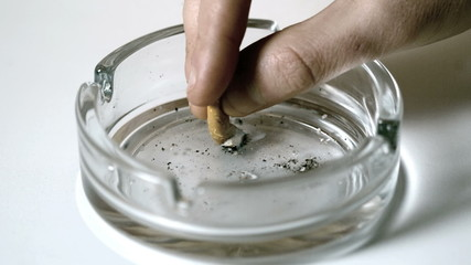 Hand extinguishing cigarette in empty ashtray