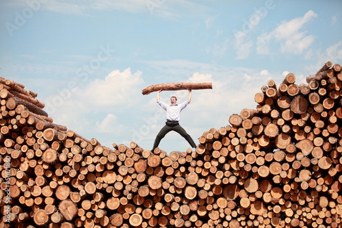 man on  top of large pile of logs, shouting, lifting heavy log