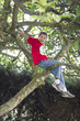 Hispanic boy climbing tree