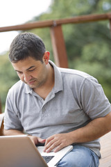 Hispanic man using laptop outdoors