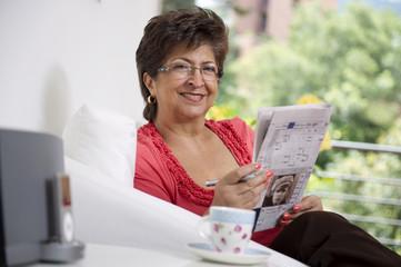 Hispanic woman reading newspaper
