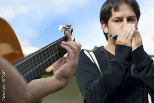 Hispanic friends playing guitar and harmonica