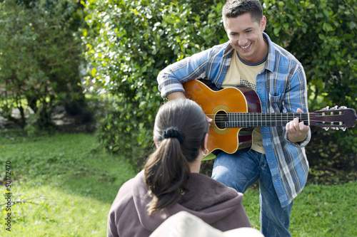 Hispanic man playing guitar for girlfriend