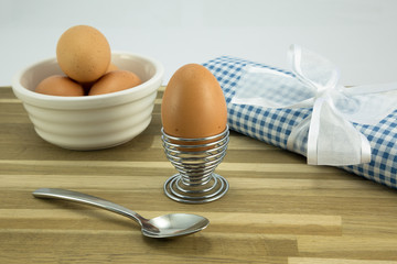 Egg,eggcup,spoon,bowl and napkin with ribbon.