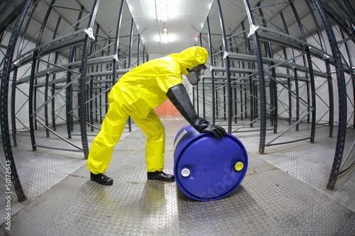 fully protected  technician,rolling a barrel wh toxic substance