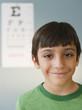 Smiling Hispanic boy having eye test