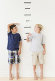 Boys measuring themselves against marks on wall