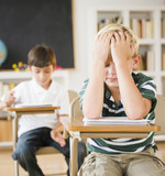 Frustrated Caucasian boy sitting at desk in classroom