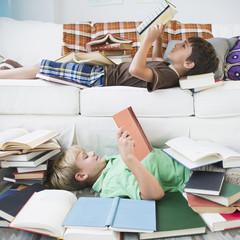 Boys reading books in living room