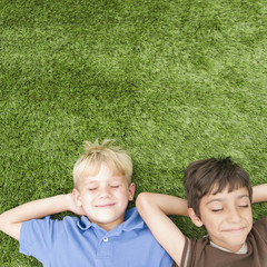 Boys with eyes closed laying in grass