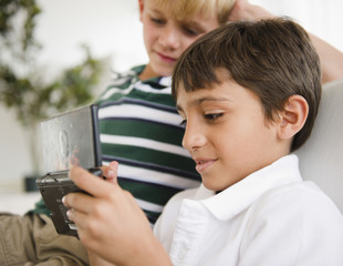 Boy watching friend playing hand-held video game