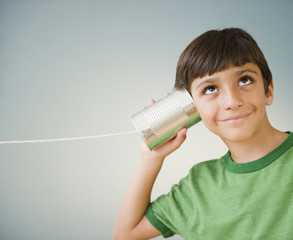 Hispanic boy listening to tin can telephone