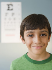 Smiling Hispanic boy having eye test
