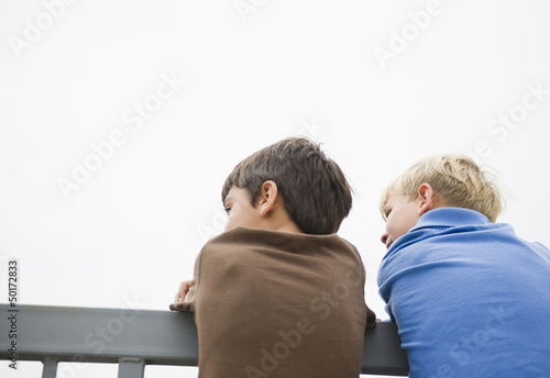 Boys standing looking over railing