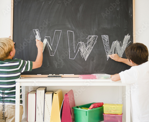 Boys drawing letters w w w on blackboard in classroom