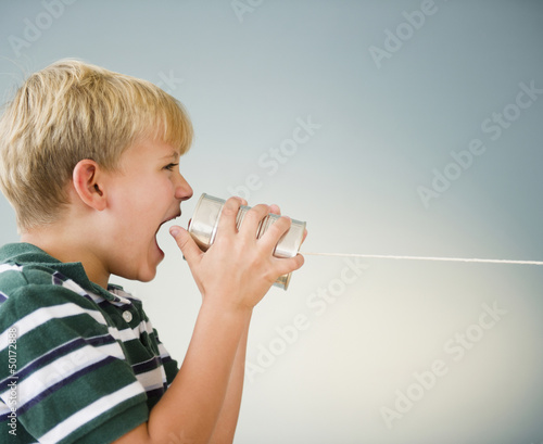 Caucasian boy shouting into tin can telephone