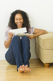 Hispanic woman sitting on floor looking at mail