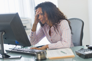 Frustrated Hispanic businesswoman using computer at desk