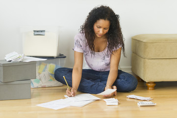 Hispanic woman sitting on floor paying bills