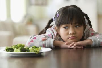 Asian girl looking at broccoli
