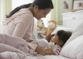Asian mother comforting daughter in bed