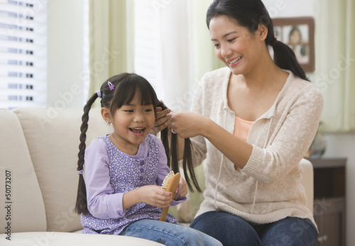 Asian mother braiding daughter's hair