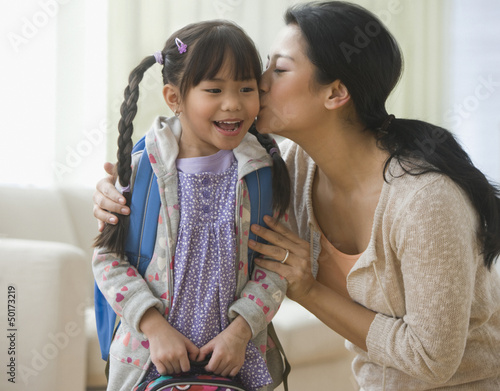 Asian mother kissing daughter