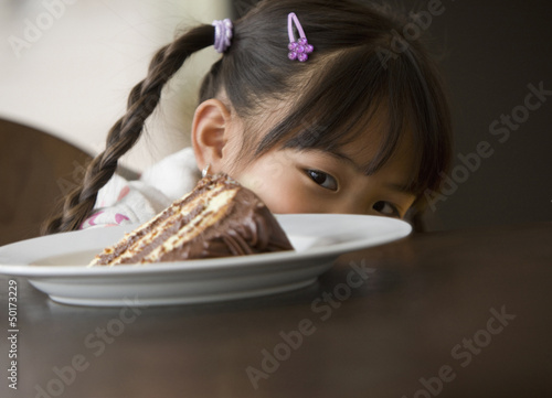 Asian girl looking at slice of cake