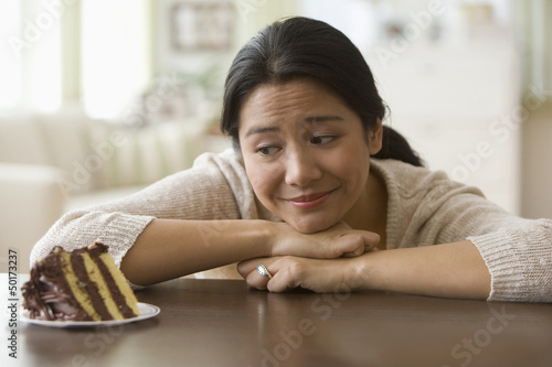 Asian woman looking at slice of cake