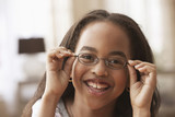 African American girl putting on eyeglasses