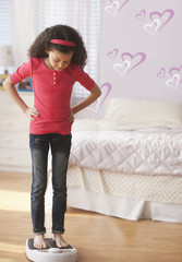 Hispanic girl standing on scales in bedroom