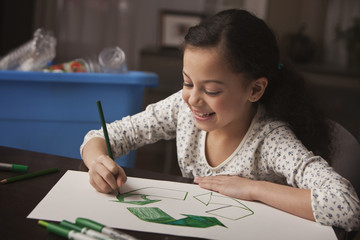 Hispanic girl drawing recycling symbol