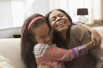 African American grandmother and granddaughter hugging on sofa