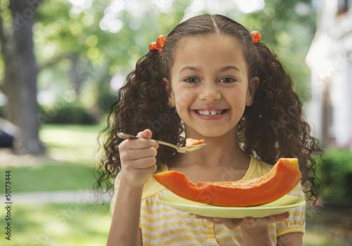 Hispanic girl eating cantaloupe