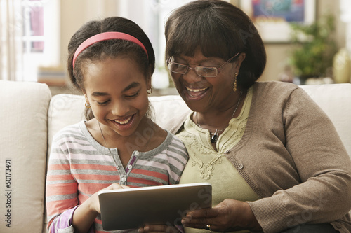 African American grandmother and granddaughter using digital tablet