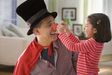 Grandfather performing magic for granddaughter