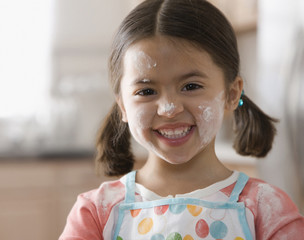 Grinning Caucasian girl with flour on her face