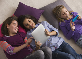 Girls laying on floor using digital tablet